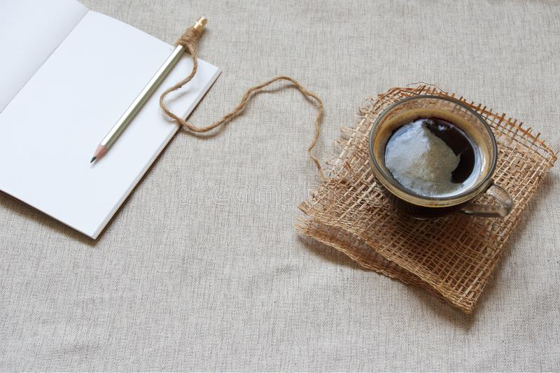 Hot coffee and blank notebook for a morning journaling routine. Hot black coffee sitting next to a blank notebook and pencil for a morning journaling routine stock image