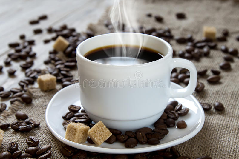 Hot black coffee in a white cup, cane sugar and roasted beans stock photos