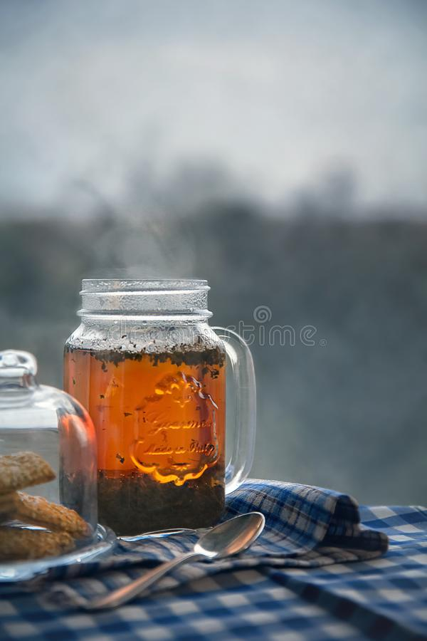 Hot black tea jar on a frosty winter day, window background royalty free stock photo