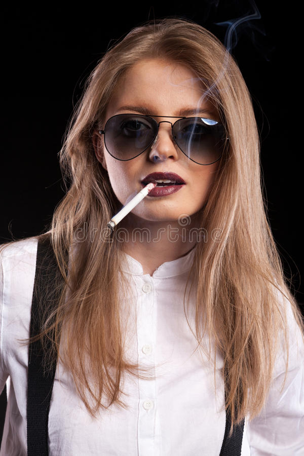Hot blonde model smoking on black background. In studio photo stock photos