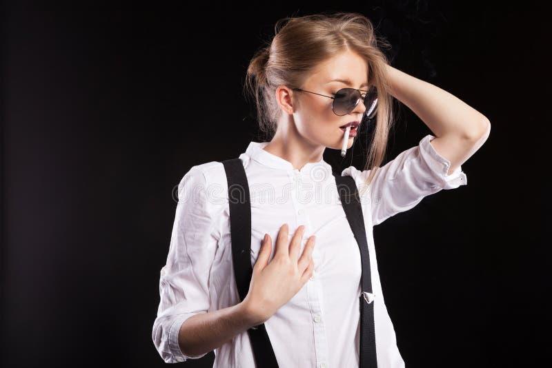 Hot blonde woman smoking on black background. In studio photo stock image