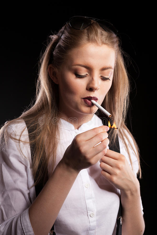 Hot blonde woman smoking on black background. In studio photo stock images