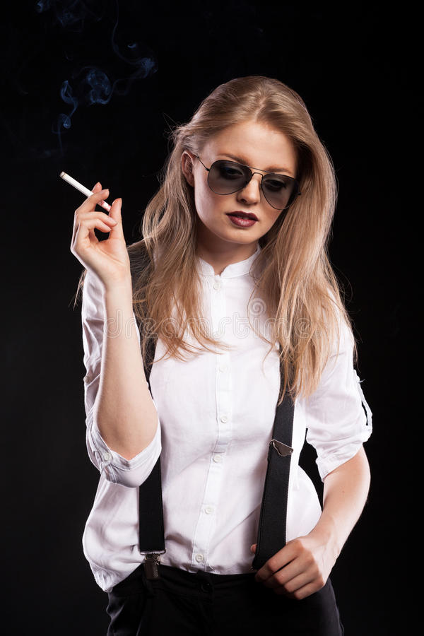 Hot blonde woman smoking on black background. In studio photo stock photography