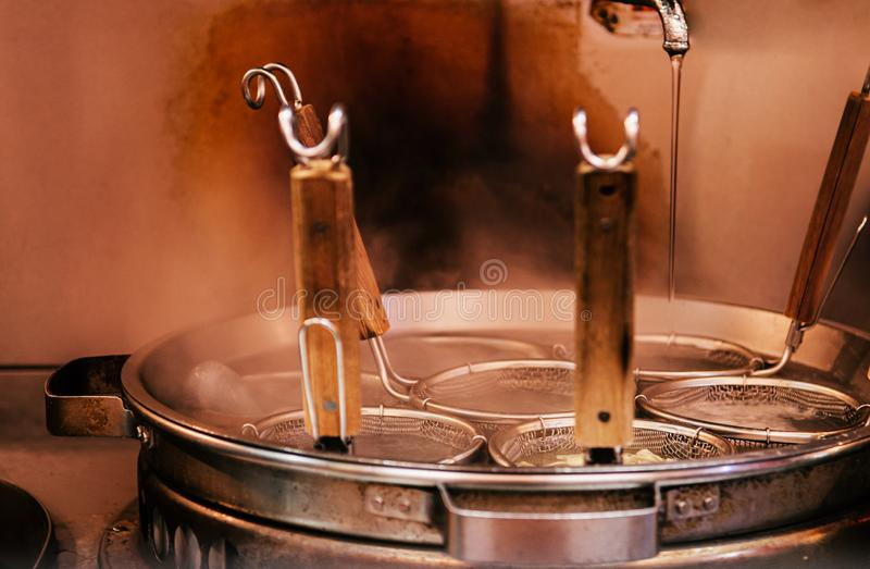 Hot boiling Ramen pot with noodle strainers and steam. Selective focus stock photos