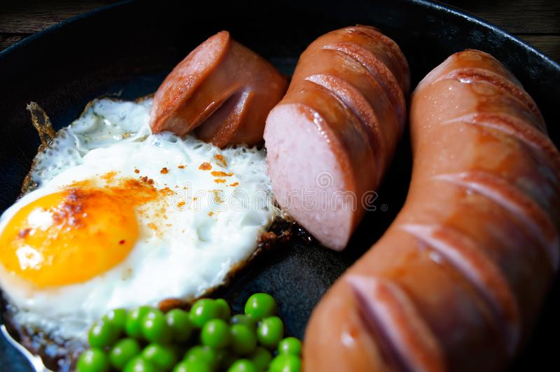 Hot breakfast in a pan. Of fried sausages and peas stock photos