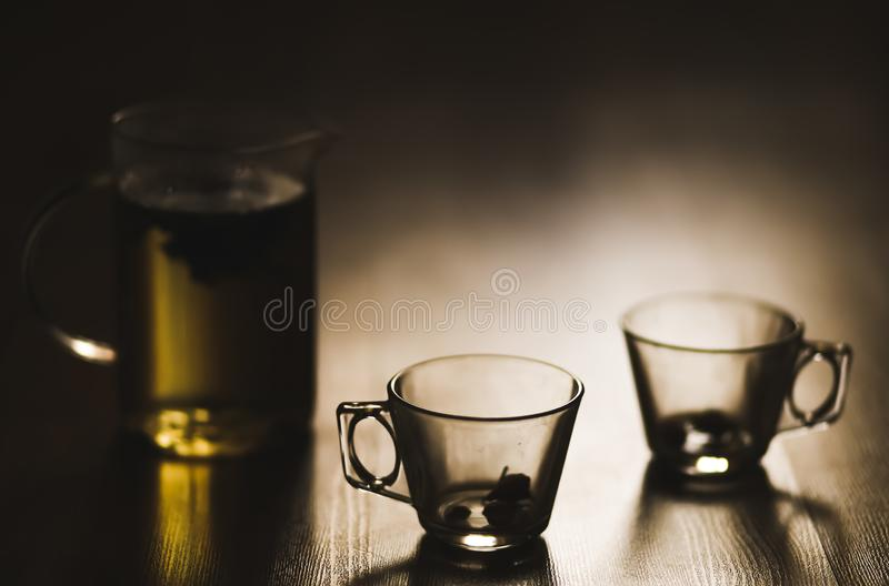 Hot brewed tea in transparent teapot and two cups on wooden background stock photo