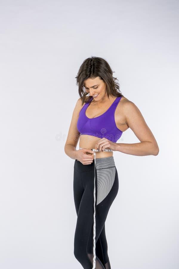 Hot Brunette Fitness Model van haar waakzaamheid tegen een witte achtergrond royalty-vrije stock afbeelding