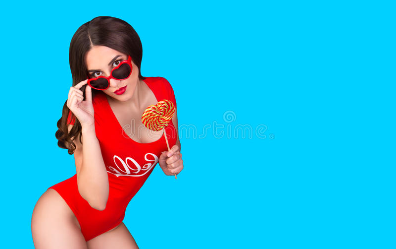 Hot brunette in a red swimsuit and glasses with hearts. young woman on a blue background. stock photos