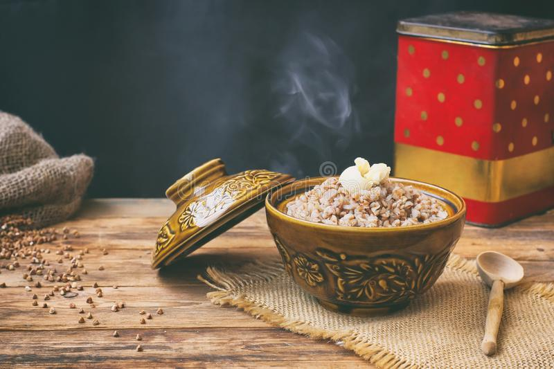 Hot buckwheat porridge with butter in a ceramic pot royalty free stock image