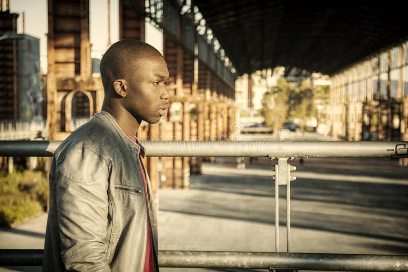 Hot buff black man posing. Portrait of a young black man in urban environment wearing red shirt and grey leather jacket stock photo