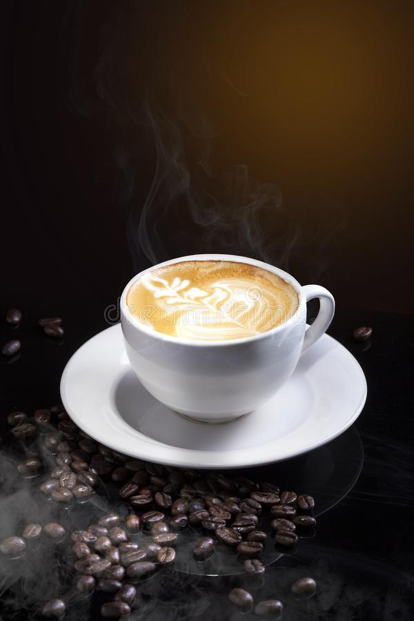 Hot cappuccino coffee with latte art in a white cup on a table sprinkled with coffee beans, isolated in dark shades and with a royalty free stock photos