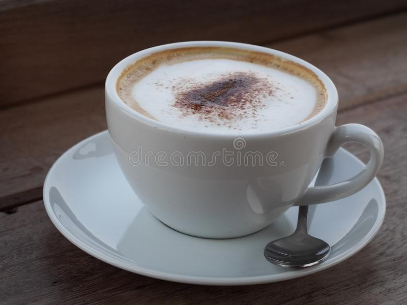 Hot cappuccino with full fine bubble cream little cacao powder served in white ceramic coffee cup stock photo