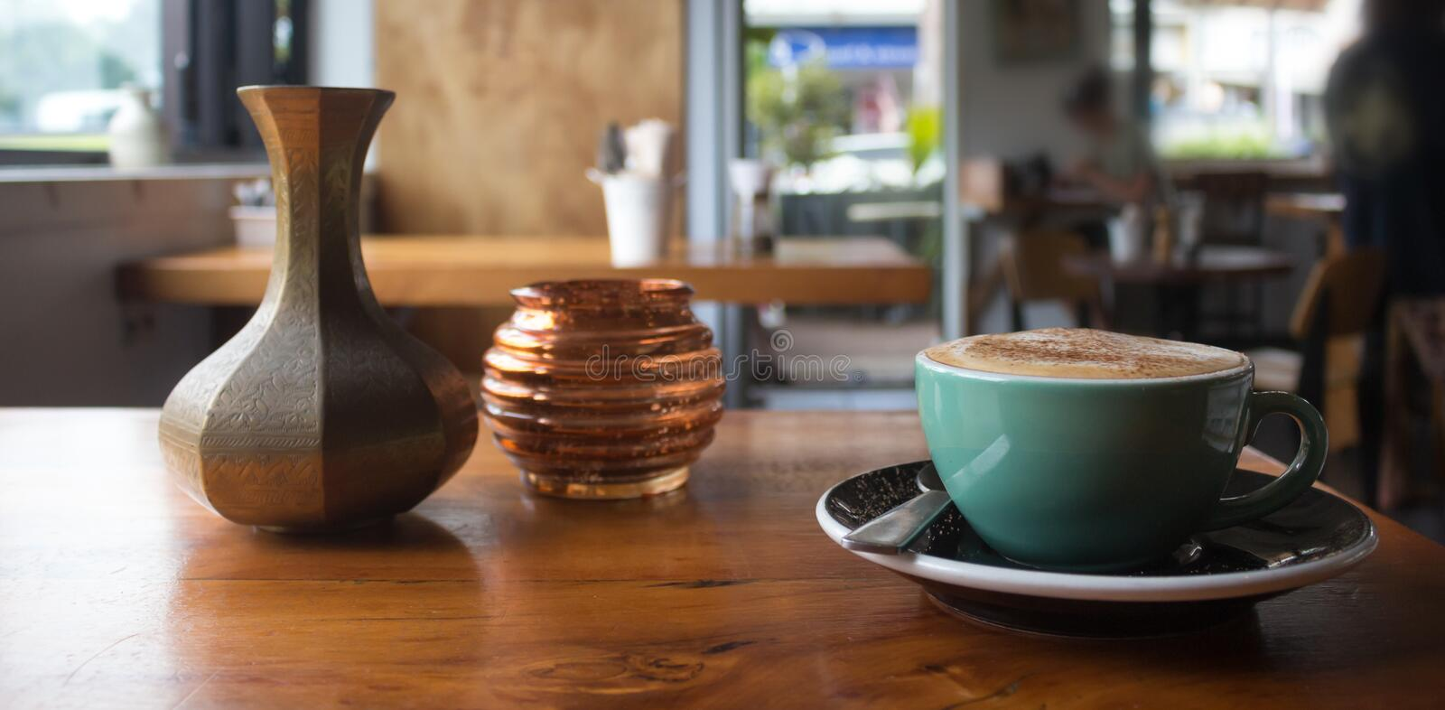 Hot cappuccino on a table inside a coffee shop. A green cup with hot cappuccino on a table inside a coffee shop in New Zealand royalty free stock photo