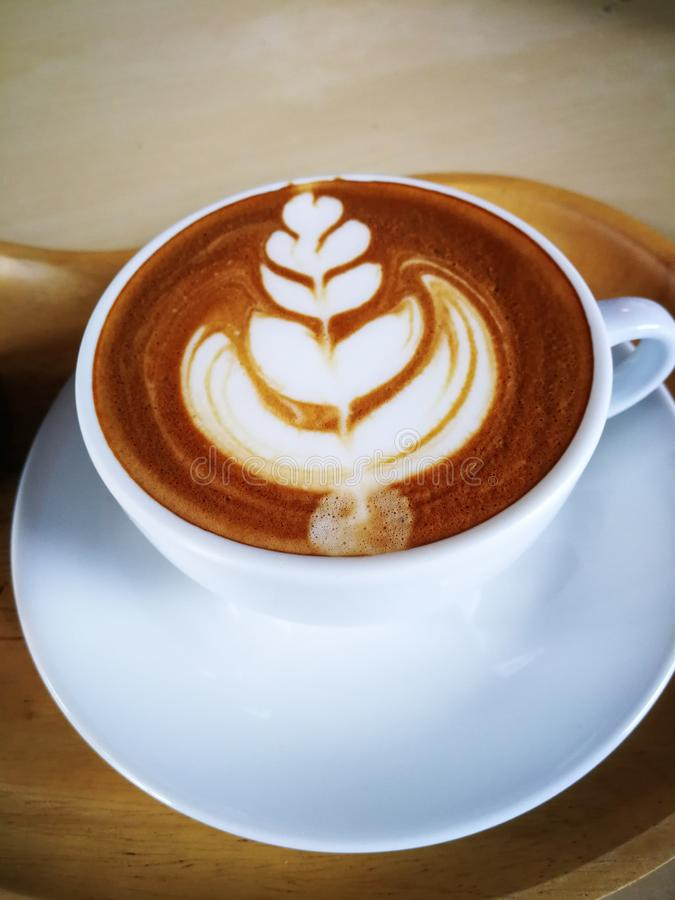 Hot cappuccino in a white cup, placed on a wooden floor stock photography