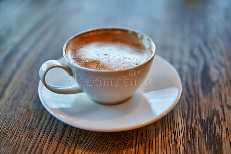 Hot Cappuccino In White Cup On Wooden Table stock photo