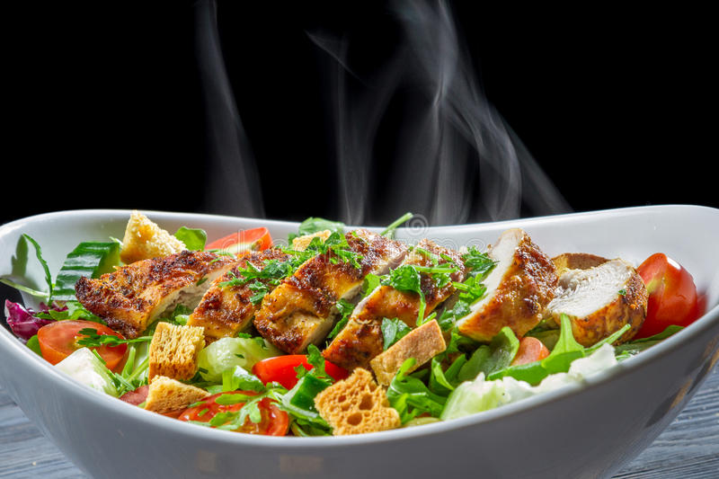 Hot chicken Caesar salad with vegetables royalty free stock photos