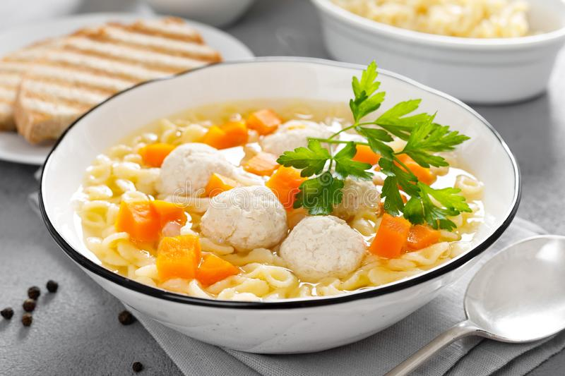 Hot chicken soup, broth with meatballs, carrot, pasta and fresh parsley royalty free stock photos