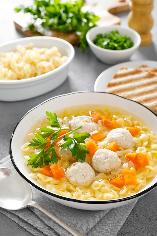 Hot chicken soup, broth with meatballs, carrot, pasta and fresh parsley royalty free stock photography