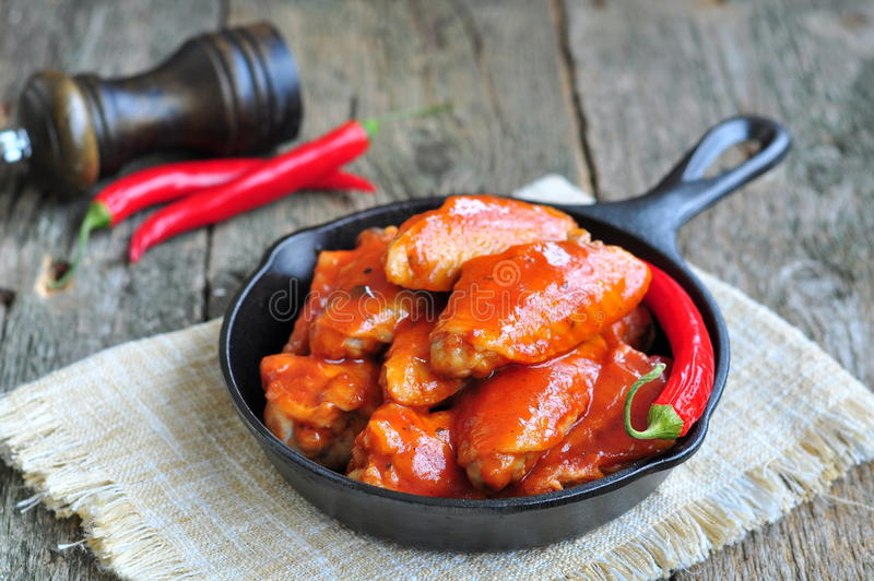 Hot Chicken Wings Barbecue in Black Saucepan isolated. CHot Chicken Wings Barbecue in Black Saucepan isolated stock photos