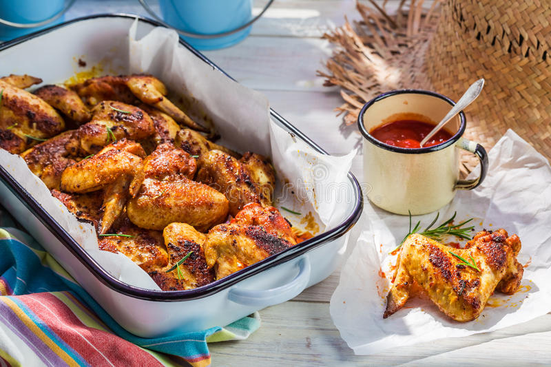 Hot chicken wings with barbecue sauce in summer kitchen. On old wooden table stock photos
