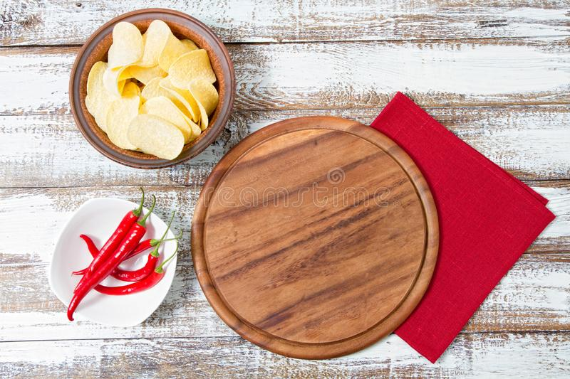 Hot chili pepper on plate,cutting pizza desk,red napkin and potato chips on table, copy space,top view stock photos