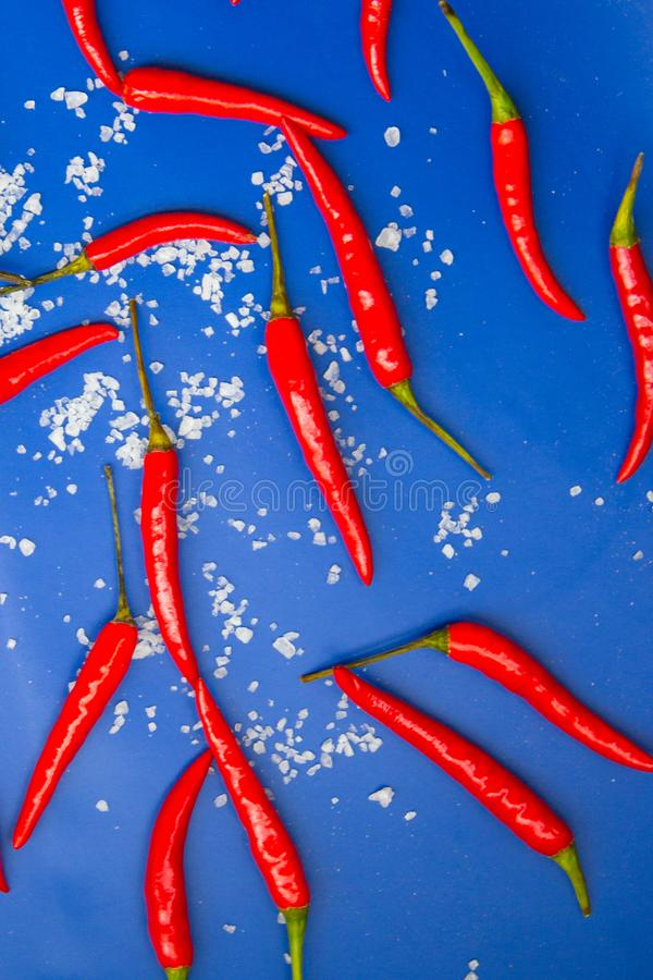 Hot chili pepper and sea salt on blue background. Top view. royalty free stock photos