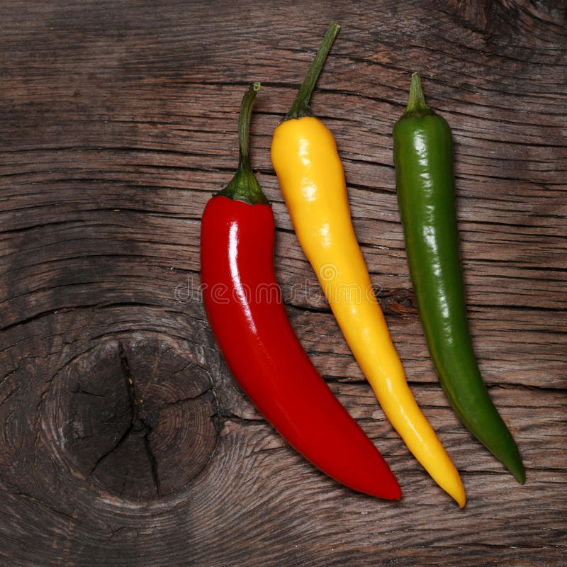 Hot chili peppers. On old wooden background stock photos