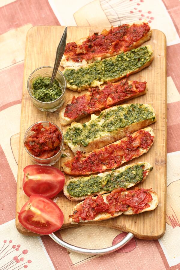 Hot chili tomato and pesto sauce, sliced roasted italian ciabatta bread for cooking bruschetta sandwiches stock images
