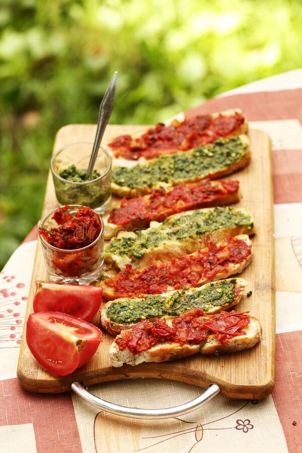Hot chili tomato and pesto sauce, sliced roasted italian ciabatta bread for cooking bruschetta sandwiches royalty free stock image