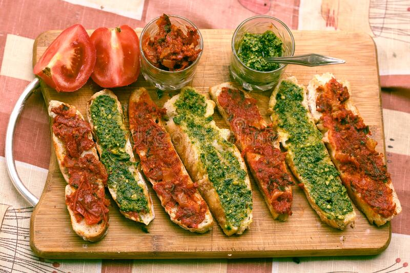 Hot chili tomato and pesto sauce, sliced roasted italian ciabatta bread for cooking bruschetta sandwiches royalty free stock photo