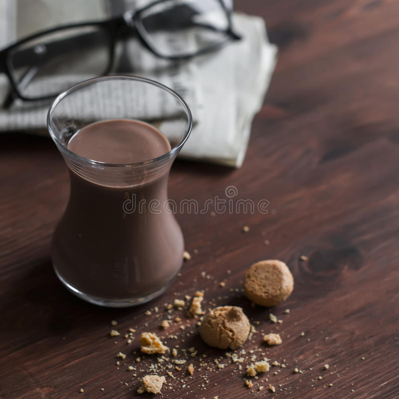 Hot chocolate, almond cookies and newspapers on dark brown wooden surface. Delicious coffee break royalty free stock photography