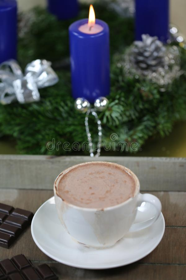 Hot chocolate with Christmas wreath in the background royalty free stock photo