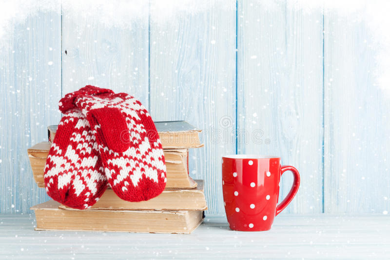 Hot chocolate cup and mittens over books royalty free stock photos