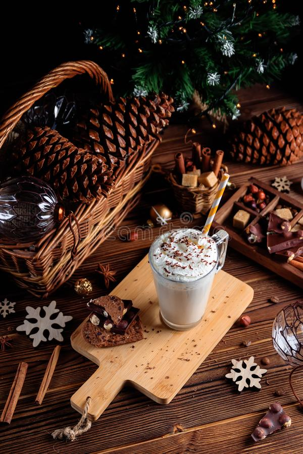 Hot chocolate drink with whipped cream. Cozy Christmas composition on a dark wooden background. Sweet treats for cold royalty free stock photo