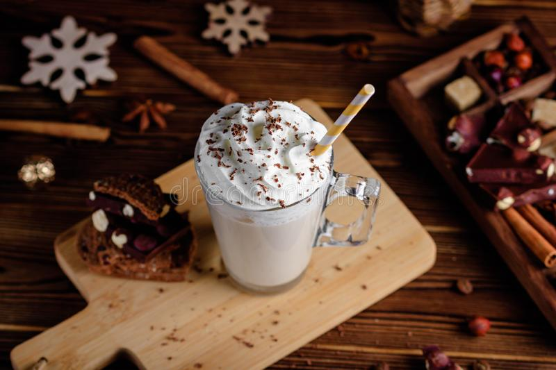 Hot chocolate drink with whipped cream. Cozy Christmas composition on a dark wooden background. Sweet treats for cold stock photography