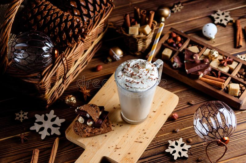 Hot chocolate drink with whipped cream. Cozy Christmas composition on a dark wooden background. Sweet treats for cold winter days. royalty free stock photo