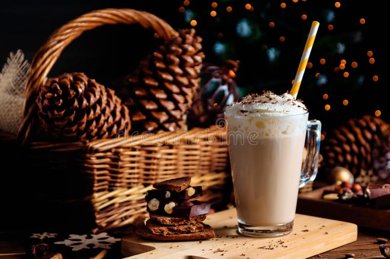 Hot chocolate drink with whipped cream. Cozy Christmas composition on a dark wooden background. Sweet treats for cold winter days. royalty free stock images