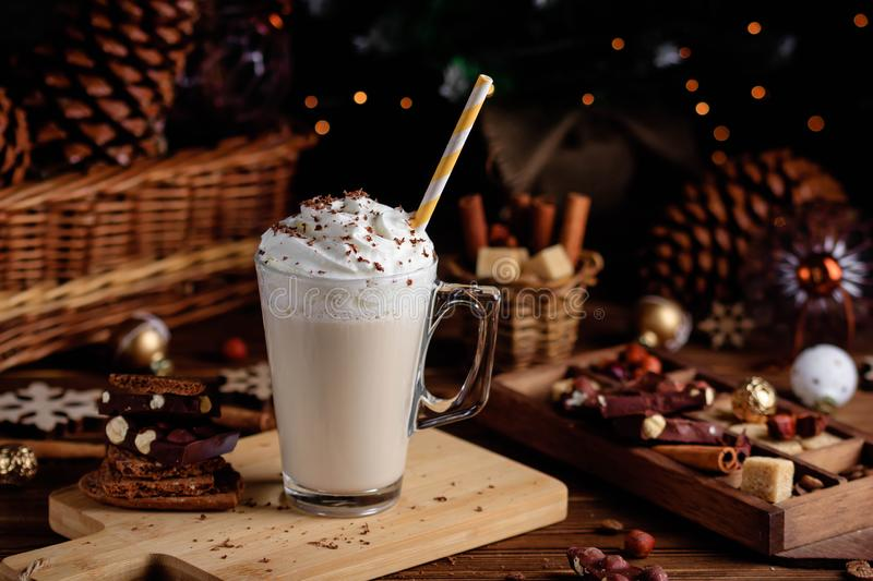 Hot chocolate drink with whipped cream. Cozy Christmas composition on a dark wooden background. Sweet treats for cold stock image