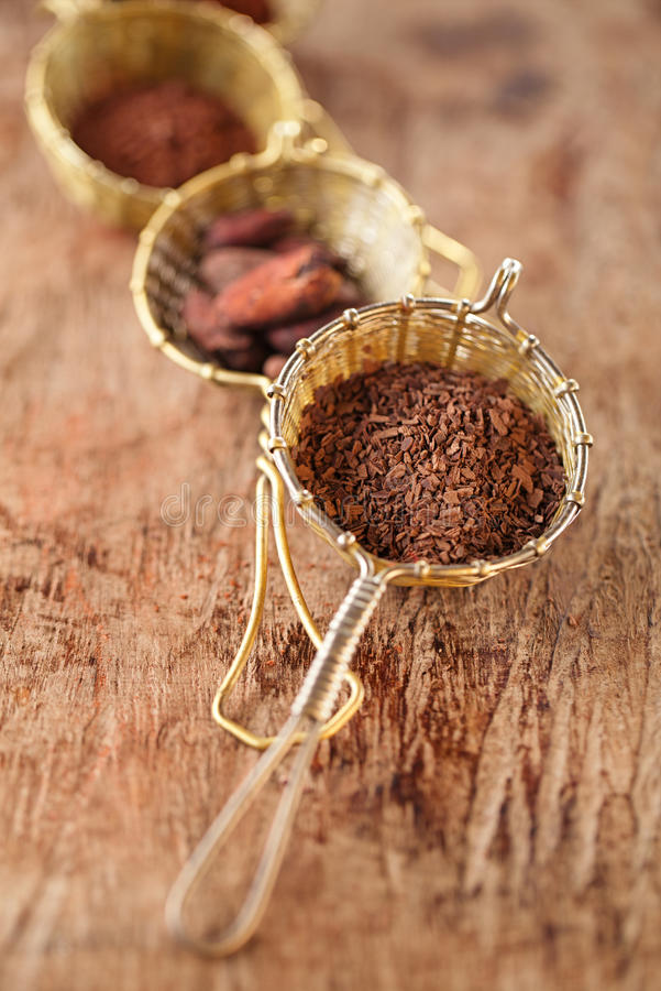 Hot chocolate flakes with chilli flavor in old rustic style silver sieve. Shallow dof stock photography