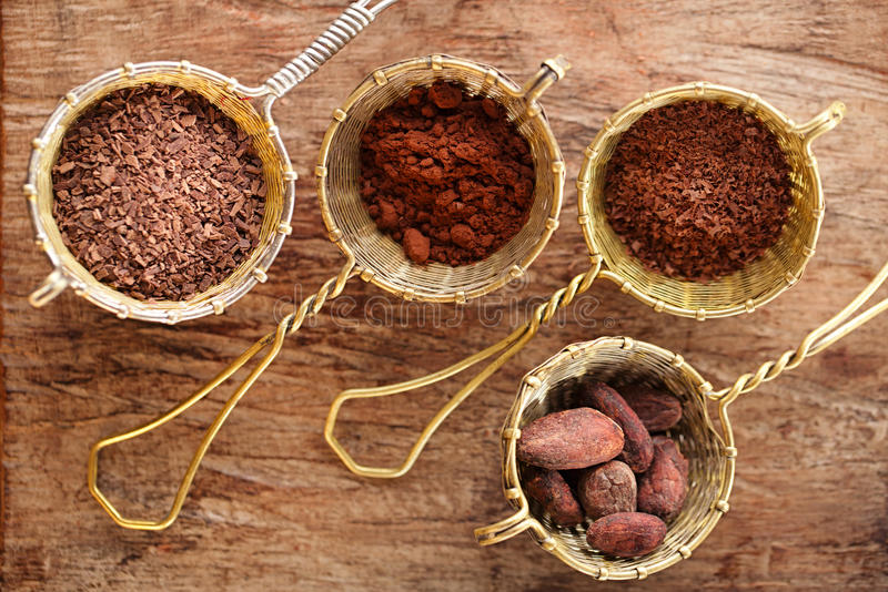 Hot chocolate flakes, grated chocolate, powder and cocoa beans. In old rustic style silver sieves on old wooden background stock photos