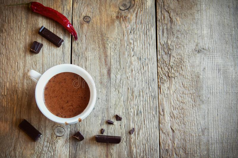 Hot Chocolate. With chili pepper and chocolate pieces over rustic wooden background. Homemade  Drink for autumn and winter holidays royalty free stock images