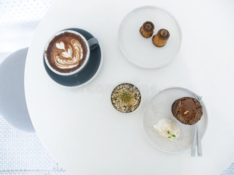 Hot chocolate latte art, assorted canneles, Chocolate brownie lava cake and cactus plants. On white table stock photography