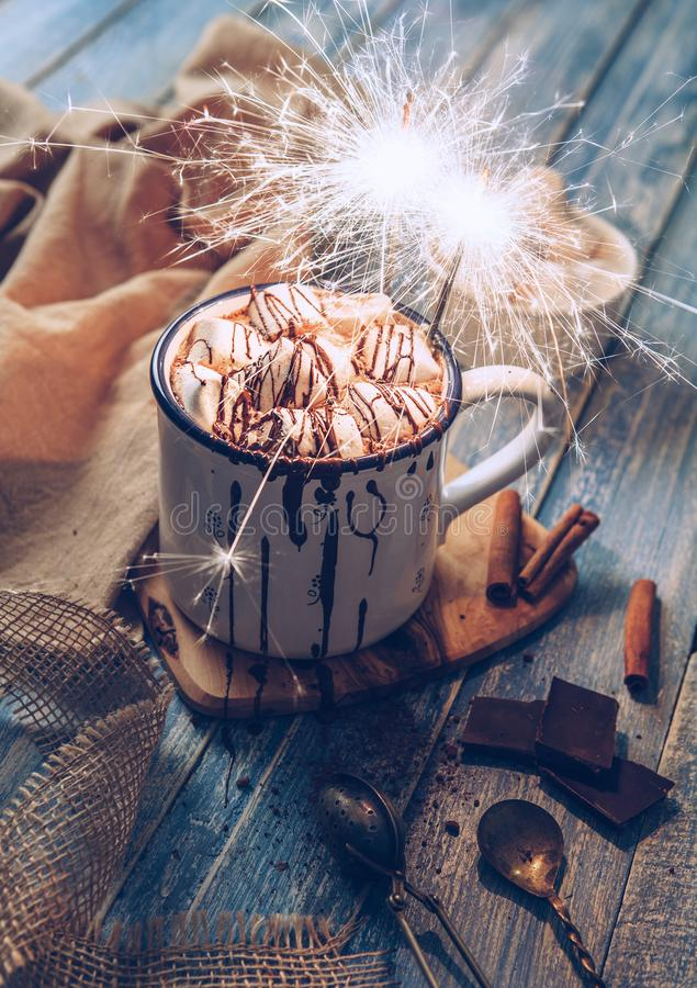 Hot chocolate with marshmallow candies and sparkles light stock image