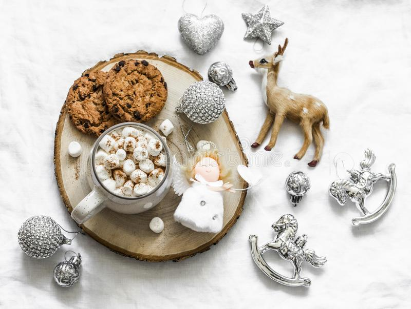 Hot chocolate with marshmallow and cinnamon and chocolate chip cookies surrounded by christmas decorations on a light background, stock image