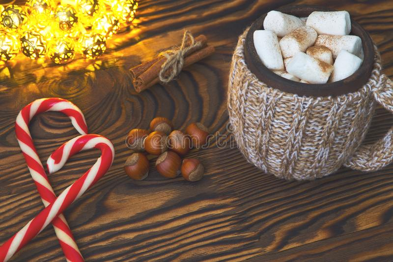 Hot chocolate with marshmallows, candy, spices and nuts on grunge dark table. Christmad card royalty free stock photography