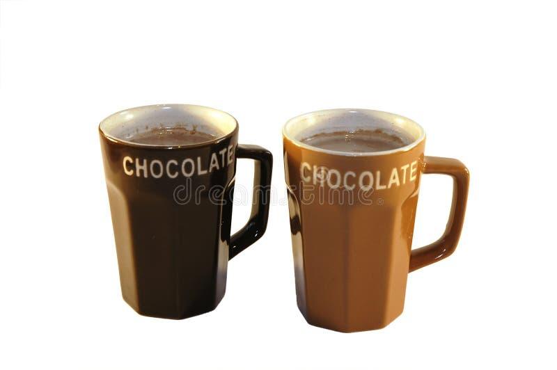 Hot chocolate milk. Two cups hot chocolate milk light background stock photos