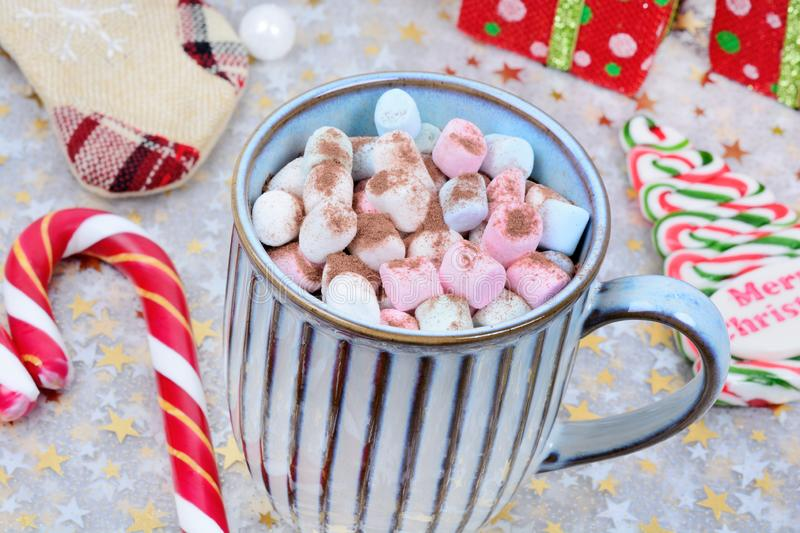 Hot chocolate in a mug with colorful marshmallow and christmas ornament on shiny table royalty free stock image