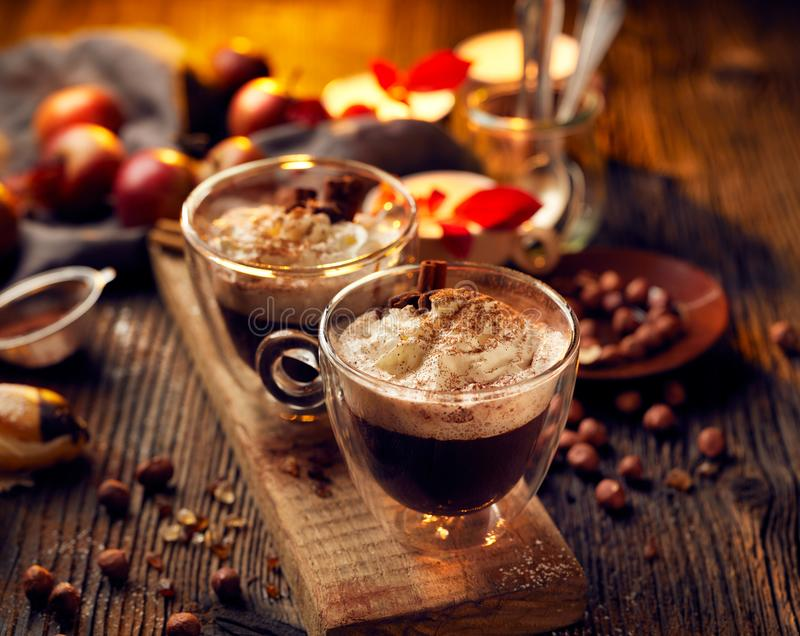 Hot chocolate with whipped cream, sprinkled with aromatic cinnamon in glass cups. On a rustic wooden table. Delicious and warming drink stock photo