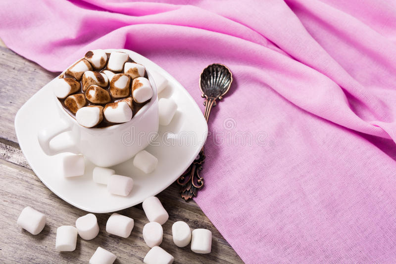 Hot chocolate in white cup with marshmallow. On the wooden table. Copy space stock photos