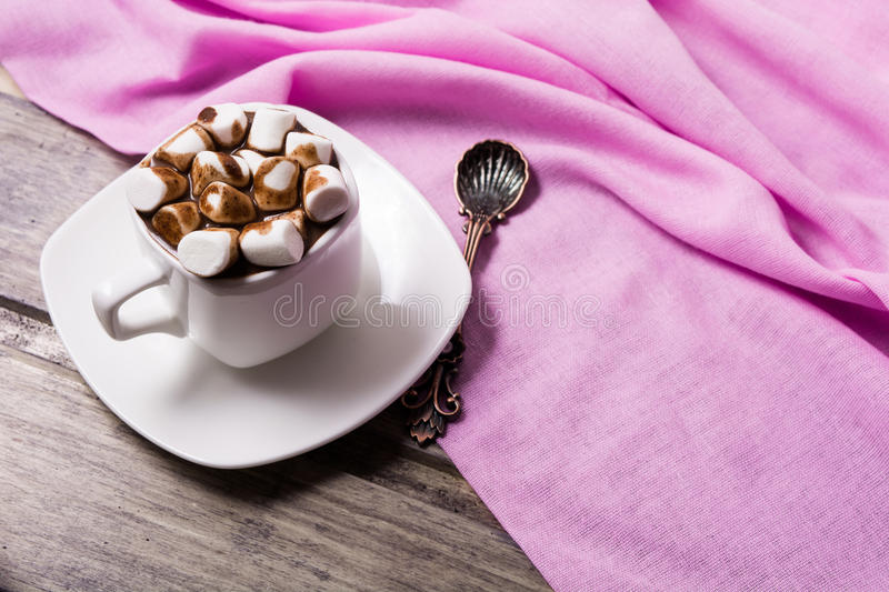 Hot chocolate in white cup with marshmallow. On the wooden table. Copy space royalty free stock image